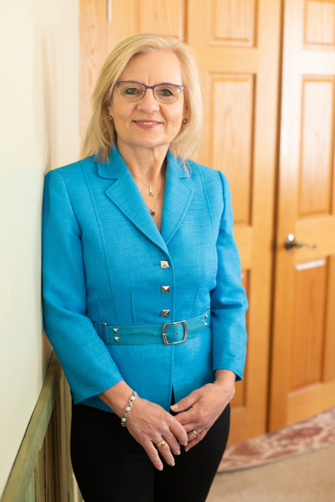 Judy Shoulak wearing a bright blue jacket with black pants in front of a light wooden door